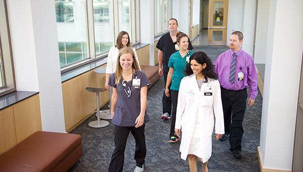 Health providers and administrators walking in hall.