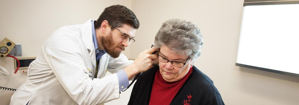Family medicine provider checks a patient's ear