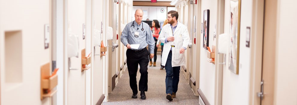 Two doctors walk down a hall together
